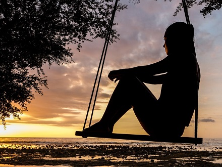 woman sitting on swing watching sunset
